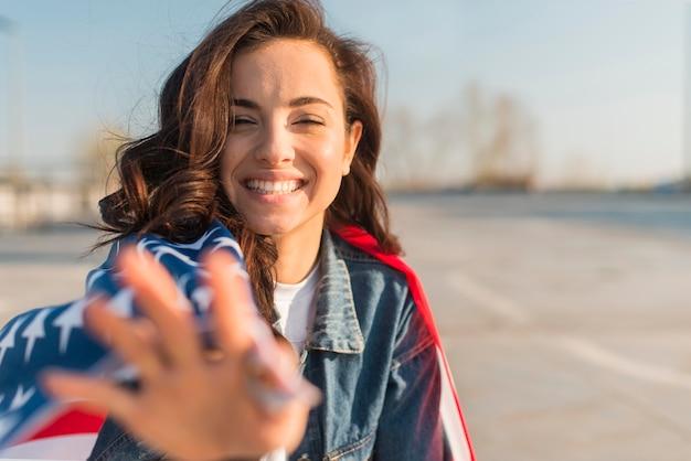Портрет женщины носить большой флаг сша и улыбается