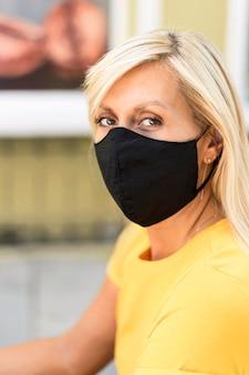 布製マスクを身に着けている女性の肖像画