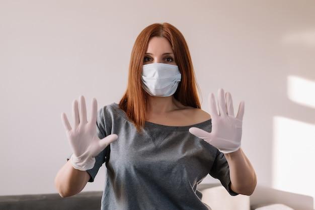 フェイスマスクとラテックス手袋を身に着けている女性の肖像画。コロナウイルスの概念