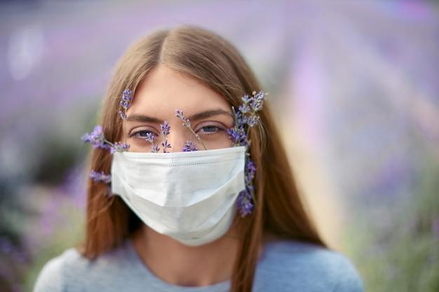 ラベンダーの花とフェイスマスクを身に着けている女性の肖像画