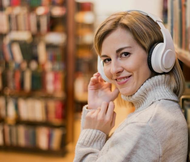 Портрет женщины носить наушники на голове в книжном магазине