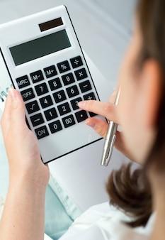 Портрет женщины с калькулятором и ручкой