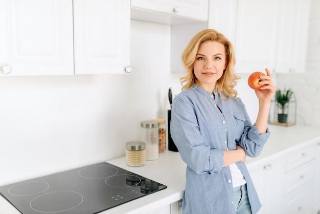 Портрет женщины с яблоком позирует на кухне с белоснежным интерьером.