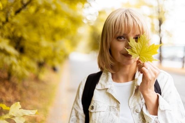Портрет женщины с осенним желтым кленовым листом рядом