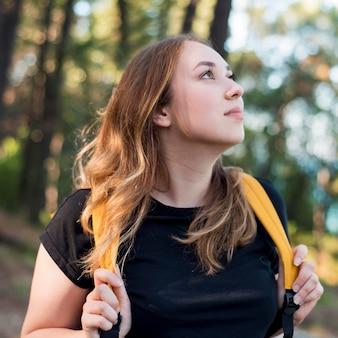 森のバックパックを持つ女性の肖像画