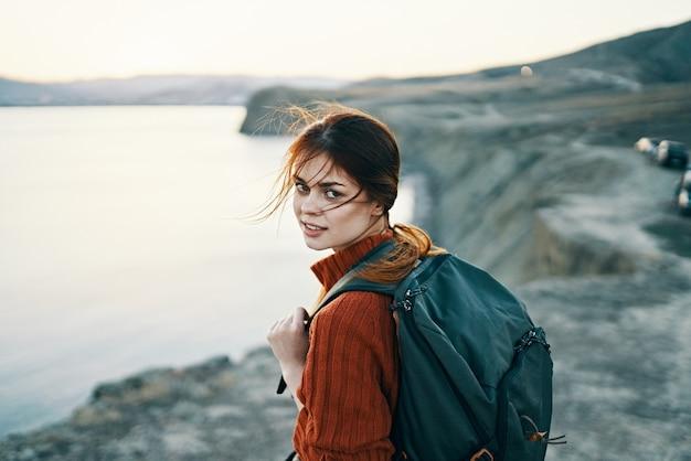 日没のトリミングされたビューで海の近くの山の自然にバックパックを持つ女性の肖像画。高品質の写真 Premium写真