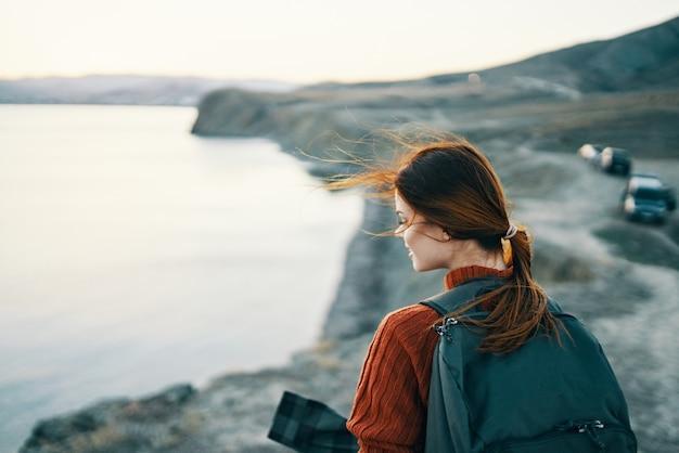 日没のクロップドビューで海の近くの山の自然にバックパックを持った女性の肖像