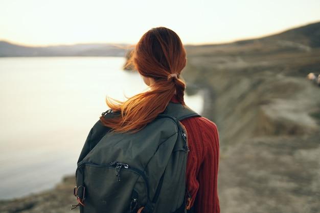 日没時の海の近くの山の自然にバックパックと女性の肖像画