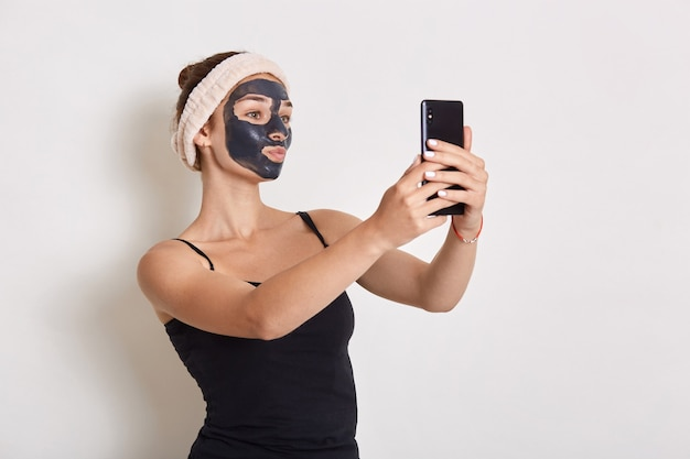 현대 스마트 폰을 손에 들고 장치 화면을보고 그녀의 얼굴에 검은 화장품 마스크를 가진 여자의 초상화