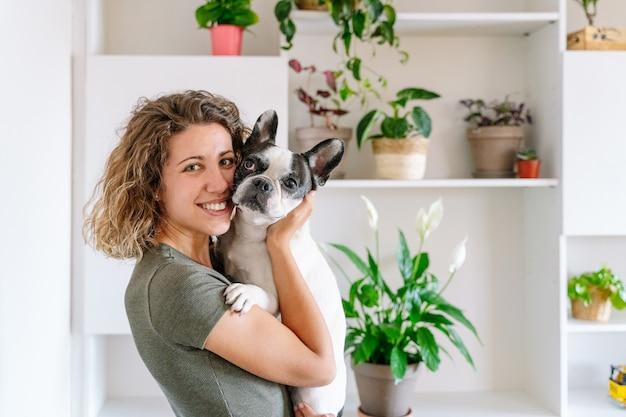 집에서 불독을 가진 여자의 초상화입니다. 식물 장식으로 개를 안고 있는 여성의 가로 보기
