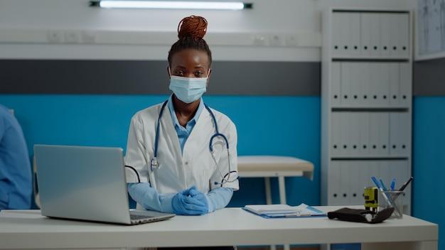 保護フェイスマスクを身に着けている医者の仕事を持つ女性の肖像画