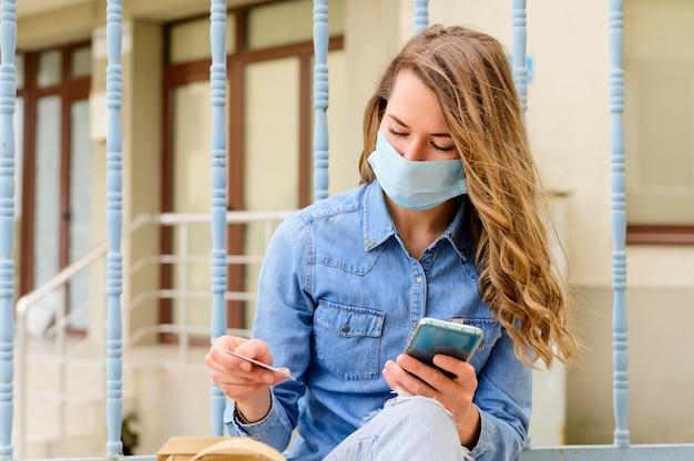 フェイスマスクチェックバッグを持つ女性の肖像画