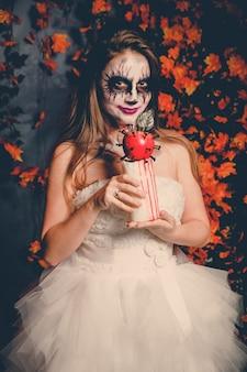 ゴーストメイクと抽象的な血まみれのリンゴを保持しているウェディングドレスの女性の肖像画。