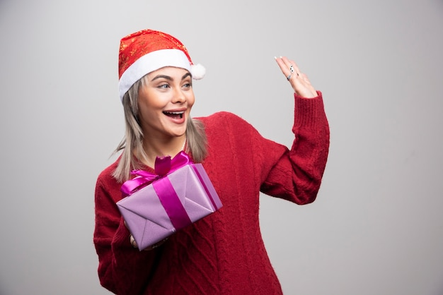 누군가에게 인사하는 선물 상자를 가진 여자의 초상화.