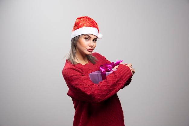 회색 배경에 선물 상자가 서 있는 여자의 초상화.