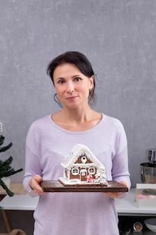 彼女の手にジンジャーブレッドハウスを持つ女性の肖像画。お正月のお菓子。垂直フレーム。