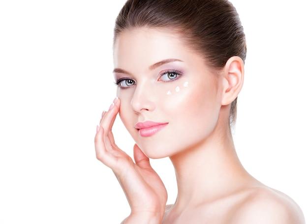 目の下に化粧クリームを塗る健康な顔の女性の肖像画。