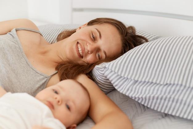 早朝に明るい部屋のベッドに横たわって、週末を楽しんで、一緒に時間を過ごして、幸せな親子関係の幼児の女の赤ちゃんまたは男の子を持つ女性の肖像画。