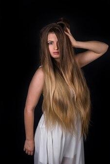 黒い壁に分離された長いブロンドの髪を持つ女性の肖像画