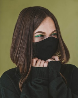 メイクとフェイスマスクを持つ女性の肖像画