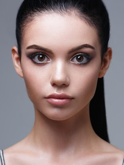 Портрет женщины с розовыми губами и выразительными глазами.