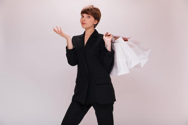 격리 된 배경에 쇼핑백을 가진 여자의 초상화. 검은 정장에 짧은 머리 백인 아가씨 흰색 배경에 포즈
