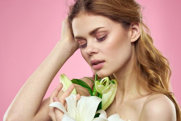 白い花を持つ女性の肖像画美しい顔ピンクの背景裸の肩。高品質の写真