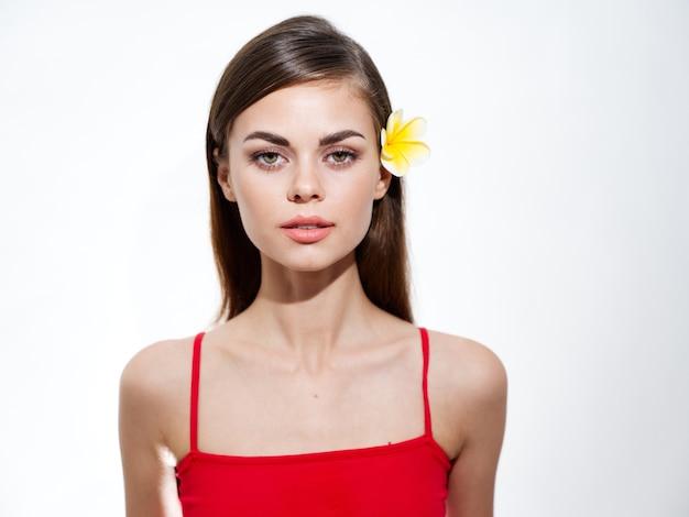 黄色い花のブルネットの赤いtシャツのトリミングされたビューを持つ女性の肖像画