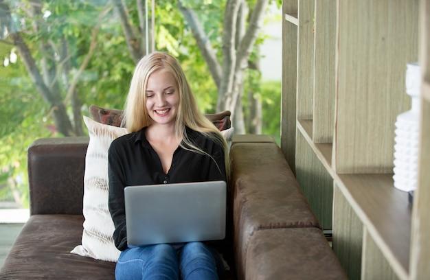 ソファでラップトップを使用している女性の肖像画。