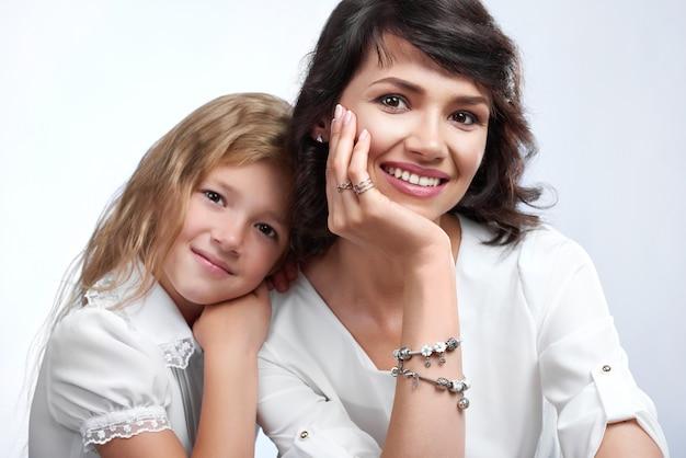 素晴らしい家族カップルの肖像画:美しい母親と彼女の小さな素敵な娘。彼らはかわいい笑顔でとても幸せです。彼らは白いtシャツを着ています。