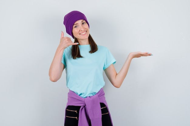 Портрет замечательной дамы, показывающей телефонный жест в блузке, шапочке и радостной вид спереди