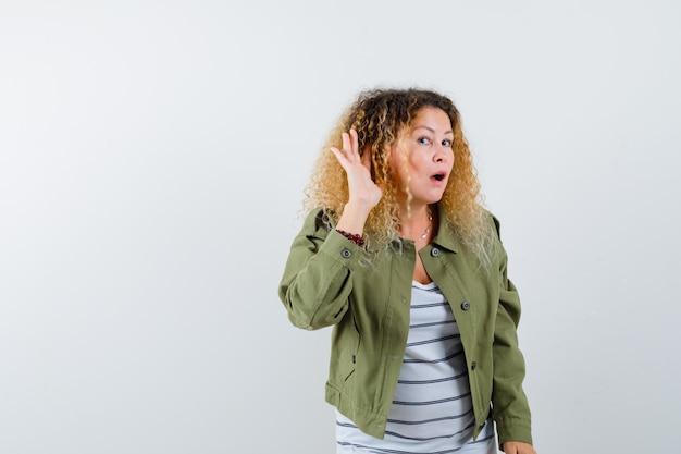 Портрет замечательной женщины, держащей руку за ухом, чтобы подслушать, в зеленой куртке, рубашке и глядя сфокусированный вид спереди