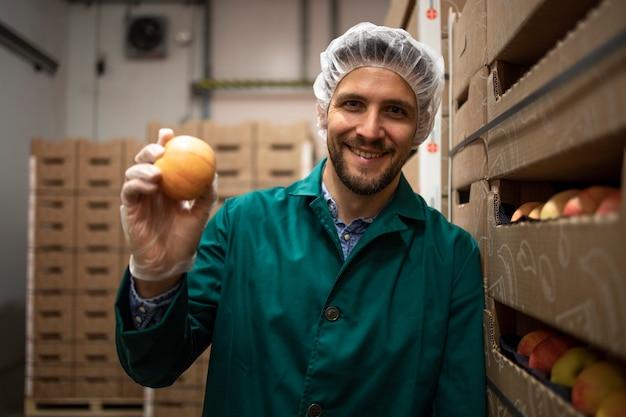 유기농 식품 공장 창 고에서 사과 과일을 들고 노동자의 초상화.