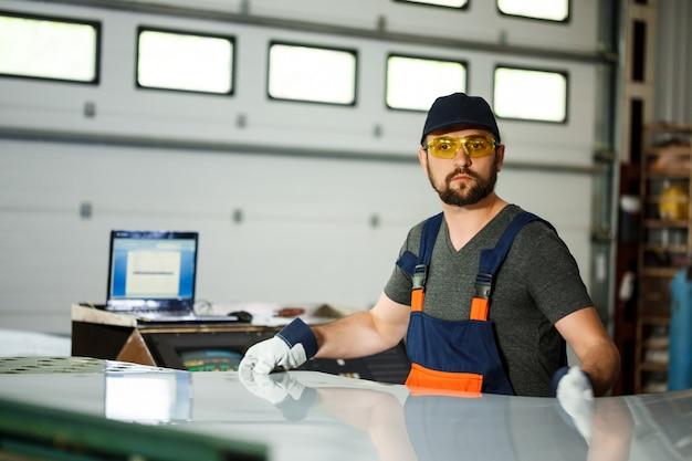 Портрет работника в спецодежде, стальной фон фабрики.
