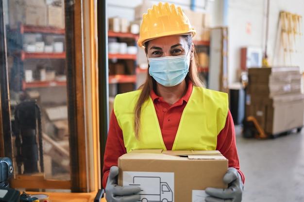 Портрет женщины работника, держащей картонную коробку внутри склада, в маске безопасности - фокус на лице
