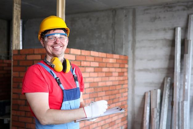 クリップボードに情報を書き込む作業者またはエンジニアの肖像画。保護用のヘルメット、メガネ、手袋を身に着けている男。建設および建物の壁