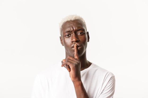 Портрет взволнованного афро-американского блондинистого парня, делающего предупреждение, шикающего на человека и недовольного нахмуренного, замолкающего, тихо, пожалуйста