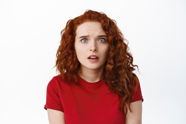 Портрет встревоженной и обеспокоенной рыжей девушки, которая выглядит встревоженной, слышит плохие новости и чувствует страх, стоя у белой стены
