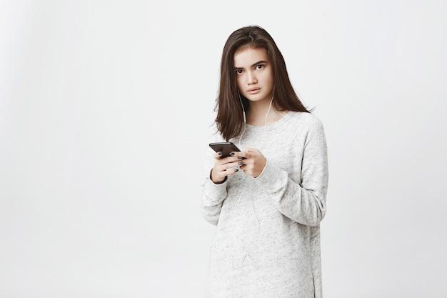 心配して欲求不満のかわいいヨーロッパの女性の肖像画、スマートフォンを押しながらイヤホンを着用