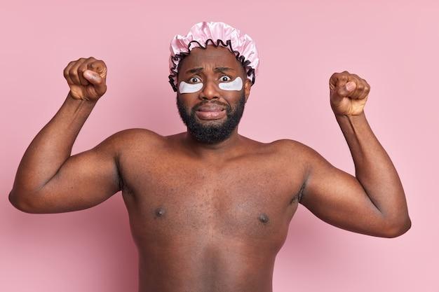 Портрет обеспокоенного темнокожего мужчины поднимает руки, сжимает кулаки, выглядит озадаченным и позирует топлес, накладывает патчи под глаза, чтобы уменьшить морщины, шляпа для ванны собирается принять душ изолированно над розовой стеной