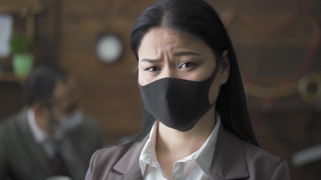 Портрет обеспокоенной брюнетки в маске в офисе