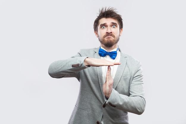 タイムアウトジェスチャーの手で立ってカメラを見ているカジュアルな灰色のスーツと青い蝶ネクタイで心配しているハンサムなひげを生やした男の肖像画。明るい灰色の背景に分離された屋内スタジオショット。