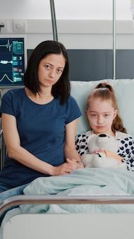 Портрет обеспокоенной матери и девочки, глядя в камеру во время обследования терапии болезни
