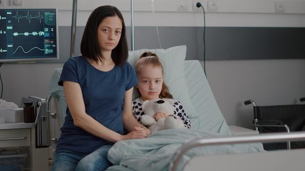 Портрет взволнованной матери, сидящей рядом с госпитализированным маленьким ребенком, глядя в камеру