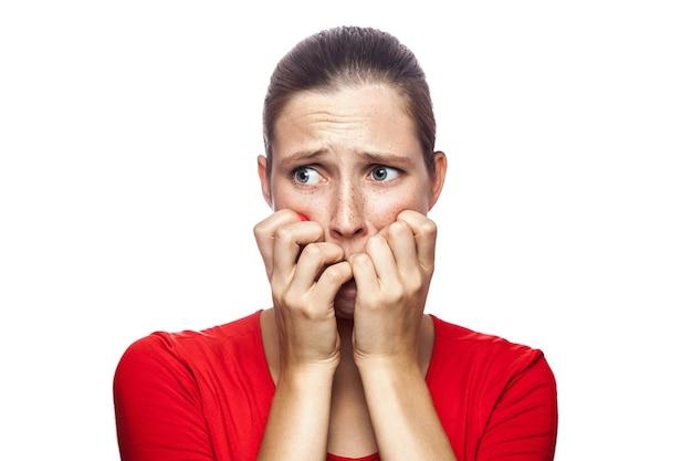 카메라를 보고 주근깨가 있는 빨간 티셔츠를 입은 걱정스러운 겁 먹은 여성의 초상화
