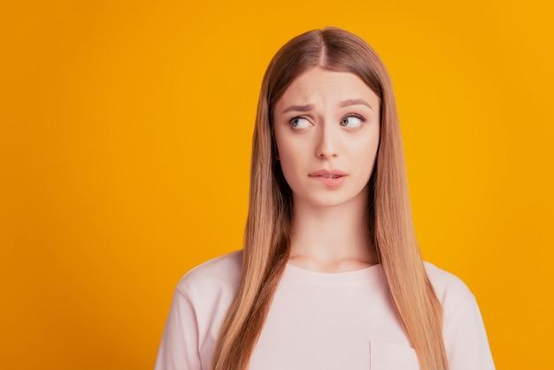 心配している問題を抱えた女性の肖像画は、黄色の背景で考える唇を見て側の空きスペースをかみます