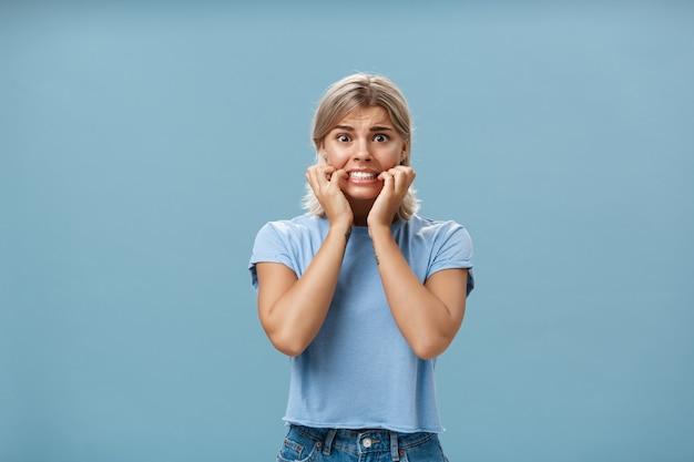 Портрет взволнованной молодой привлекательной и стильной женщины, начинающей паниковать и нервно стиснув зубы, держась за руки возле рта и хмурясь, выглядя обеспокоенной и напуганной