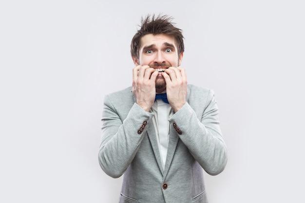 カジュアルな灰色のスーツと青い蝶ネクタイが立って、神経質に彼の爪を噛み、カメラを見て心配ハンサムなひげを生やした男の肖像画。明るい灰色の背景に分離された屋内スタジオショット。