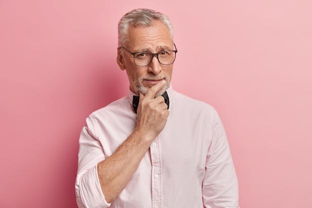 Портрет морщинистого седого пенсионера с глубокими мыслями, держит подбородок, смотрит прямо в камеру, носит очки, формальную рубашку с галстуком-бабочкой, что-то решает, изолированный на розовом фоне