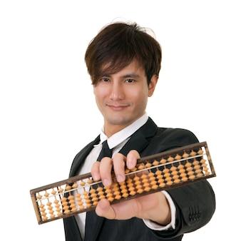 白い背景に中国の伝統的なそろばんを保持しているアジアのビジネスマンの肖像画。 Premium写真